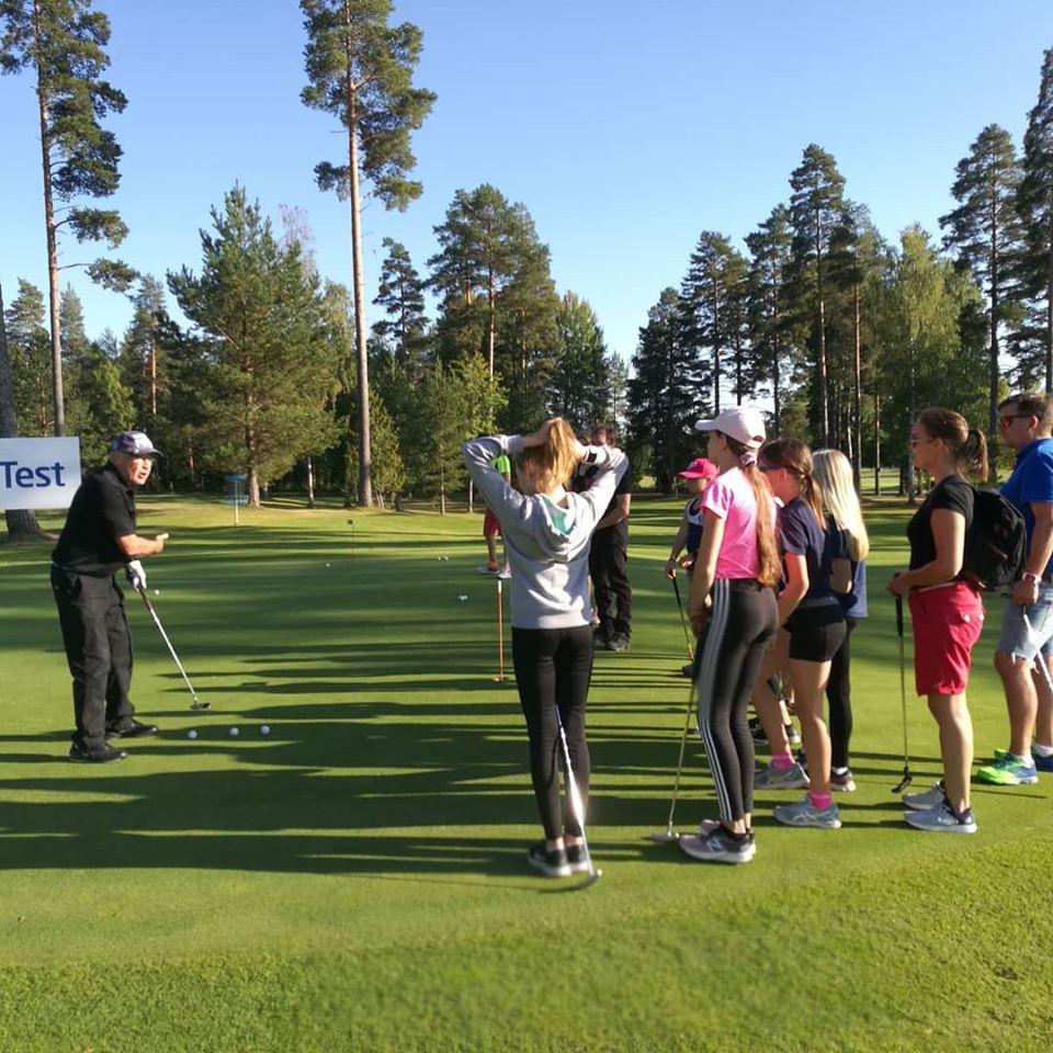 Lapsia ja aikuisia tutustumassa golfiin